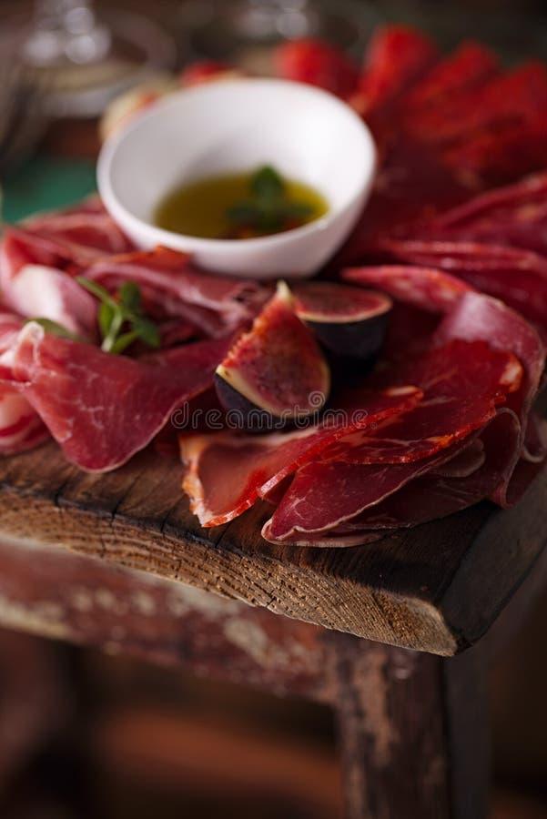 Kurerad kött och olivolja på texturerad gammal trästol arkivbilder