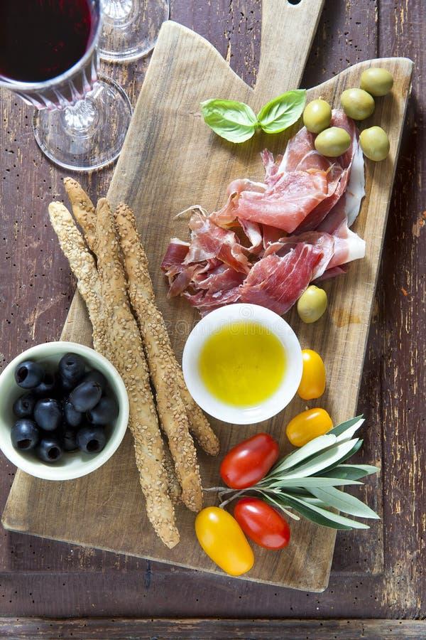 Kurerat kött på en träskärbräda med röda tomater, oliv a arkivfoto