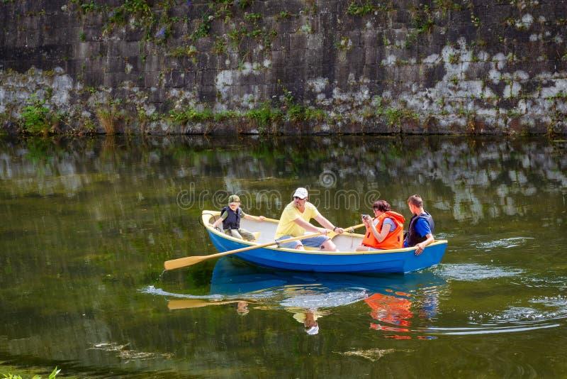 Kuressaare, ESTONIA, 2018, 14 Lipiec: Rodzinna wioślarska łódź w grodowej fosie blisko średniowiecznej ściany obrazy stock