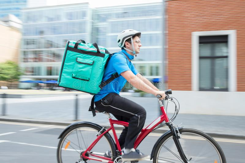 Kurier-On Bicycle Delivering-Lebensmittel in der Stadt lizenzfreie stockbilder