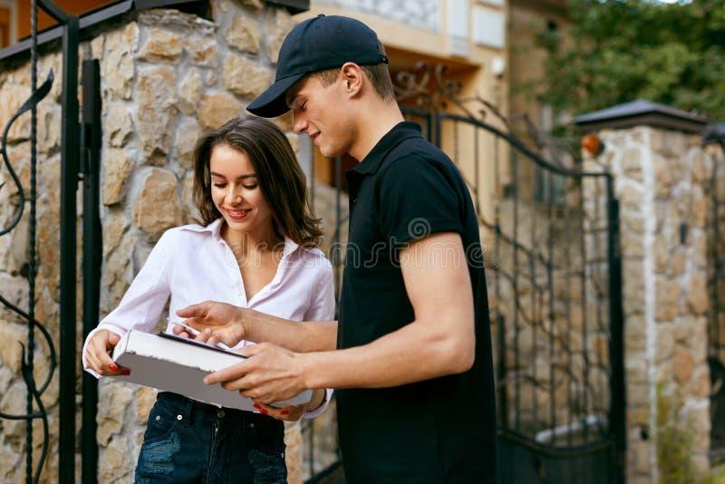 Kurier-Delivering Food To-Kunden-Haus Netter junger Lieferbote, der einen Pizzakasten hält, während Sie auf Weiß lokalisiert werd stockfotos