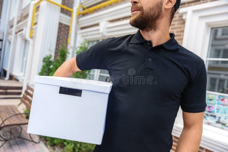 Kurier, der einen Kasten vor Haus hält stockfotos