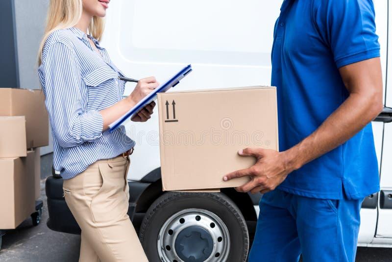 Kurier dostarcza pakunki dla kobiety zdjęcia stock
