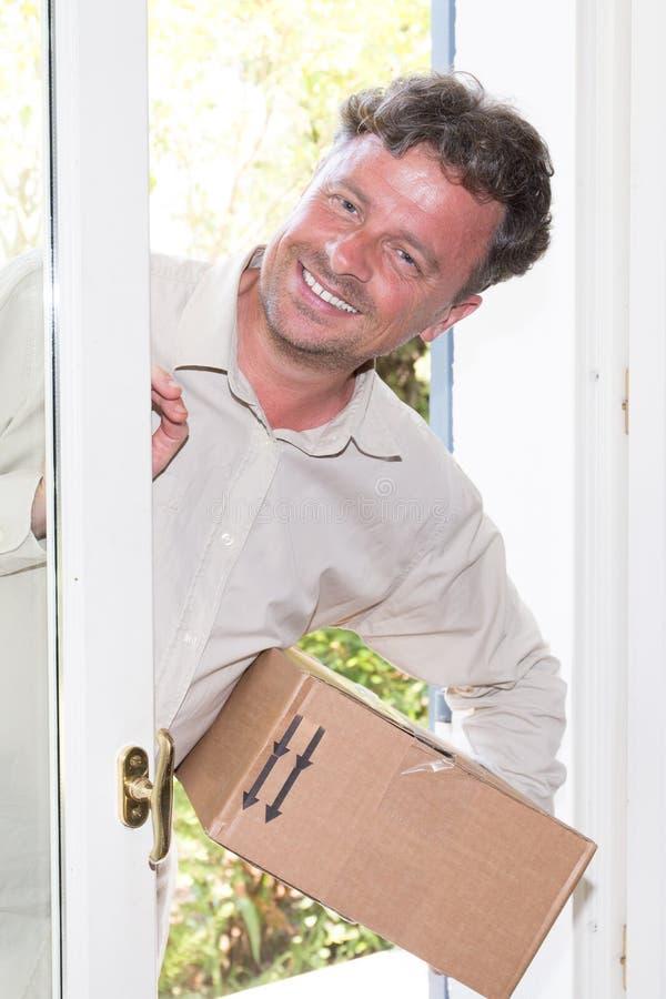 Kurier-With-Paketkasten, der zu Hause Paket liefert stockbild