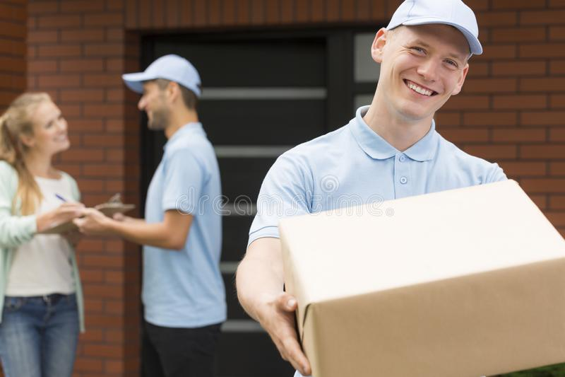 Kurier trzyma dużych brązu ono uśmiecha się i pakunek w błękita mundurze fotografia stock