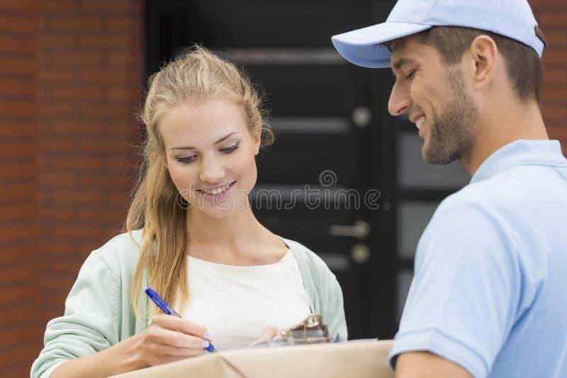 Kurier und lächelnder unterzeichnender Empfang der Frau auf Kasten stockbild