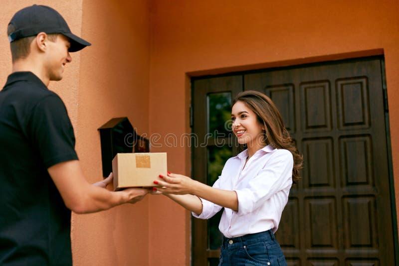 Kurierdienstservice Kurier, der Paket an Frau liefert stockfotografie