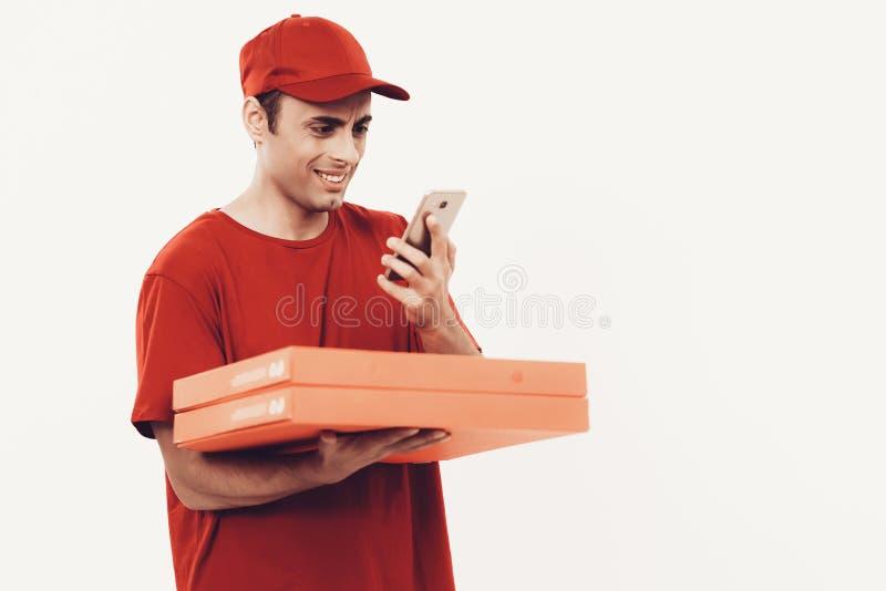 Kurir med asken i orange enhetliga blickar i telefon arkivbilder