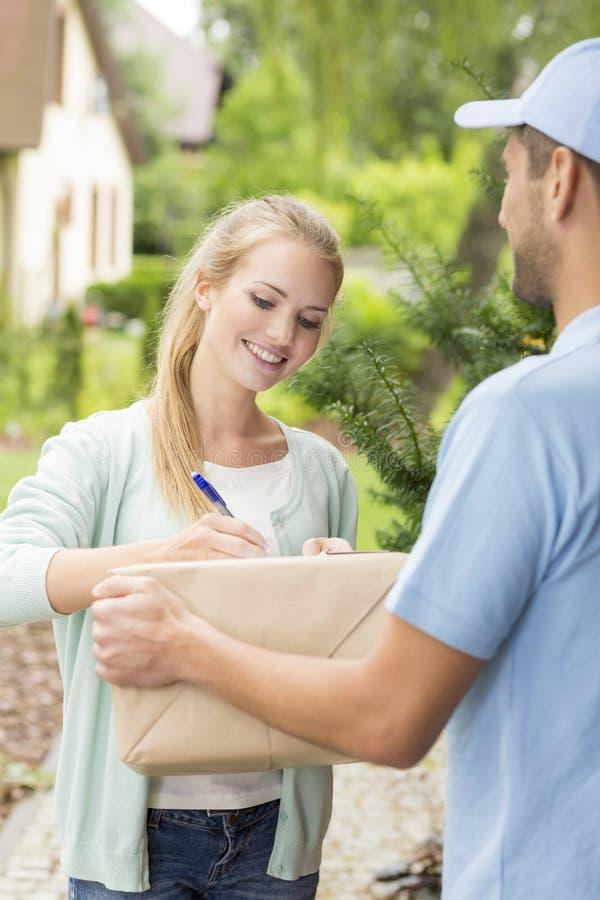 Kurir med den lyckliga unga kunden som undertecknar en leveransform royaltyfria foton