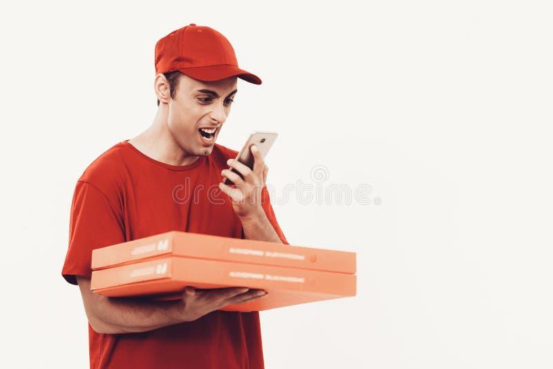 Kurir med pizza i enhetliga rop in i telefonen royaltyfri bild