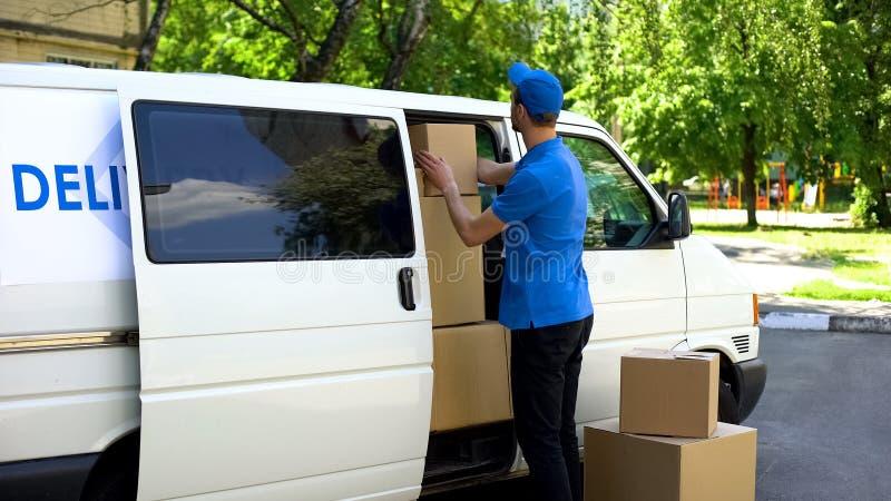 Kuriren som ut tar, boxas från skåpbilen, service för det rörande företaget, förflyttningsfirma royaltyfri bild