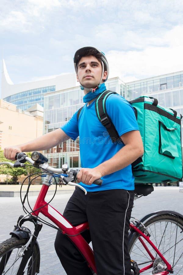 KurirOn Bicycle Delivering mat i stad royaltyfria foton