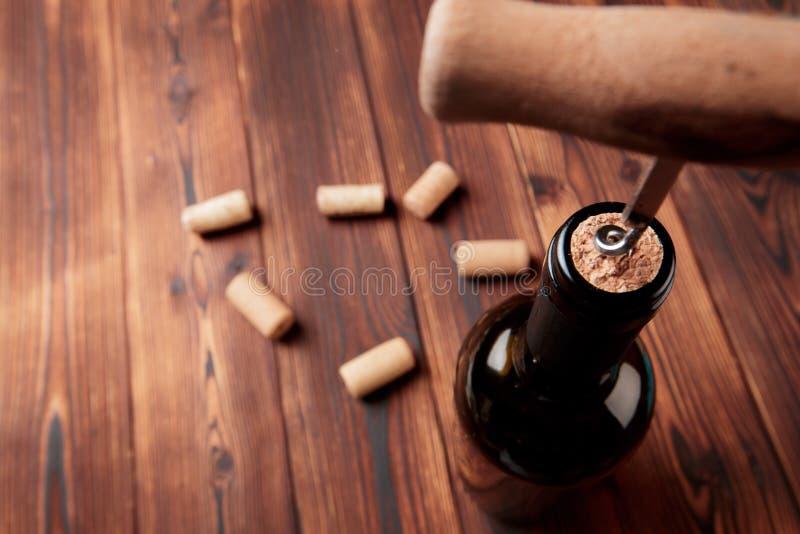 Kurketrekker en fles wijn op de raad - Beeld stock afbeeldingen
