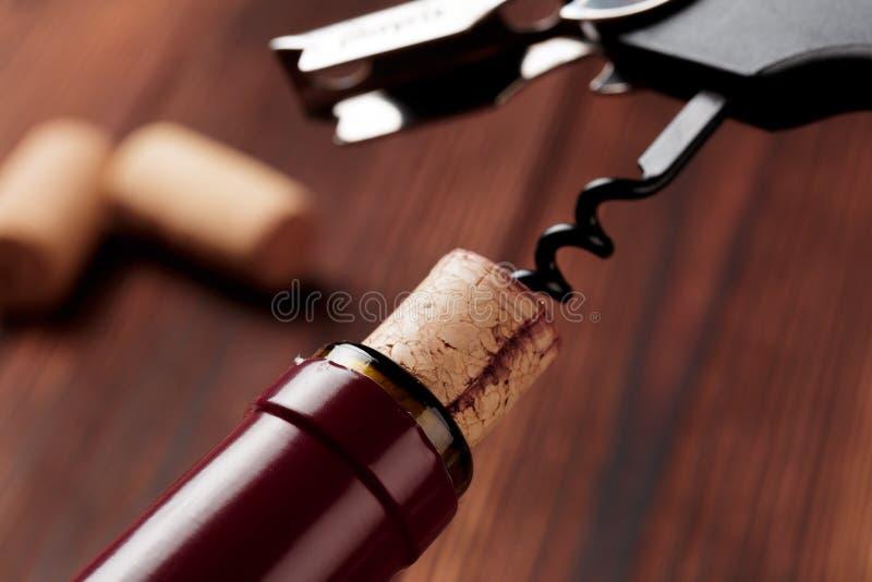 Kurketrekker en fles wijn op de raad - Beeld stock fotografie