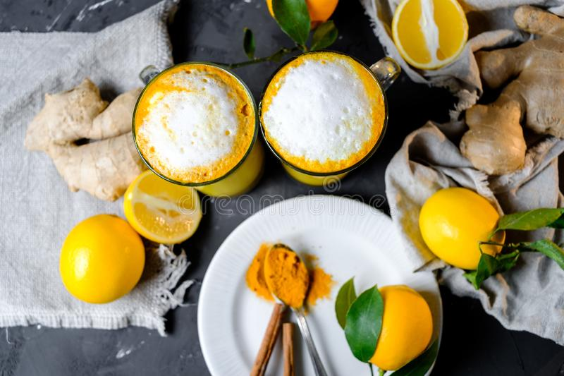 Kurkuma latte of gouden melk in glazen met gember en citroenen op een zwarte lijst stock foto's