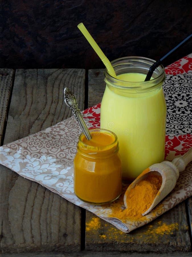 Kurkumapoeder, deeg en latte op houten achtergrond Ayurvedic gezonde gouden drank met kokosmelk en ghee voor schoonheid stock fotografie