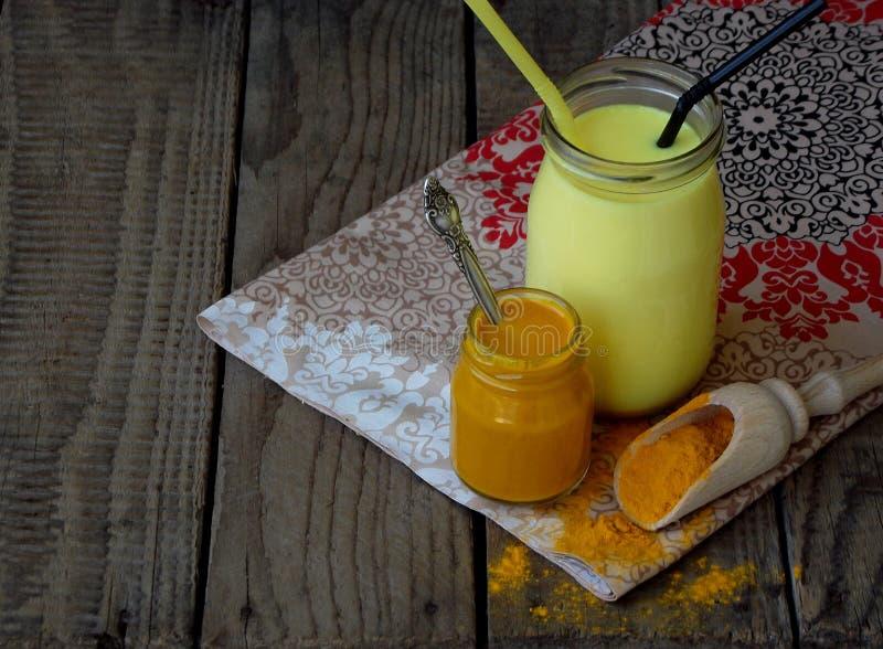 Kurkumapoeder, deeg en latte op houten achtergrond Ayurvedic gezonde gouden drank met kokosmelk en ghee voor schoonheid en hij stock foto