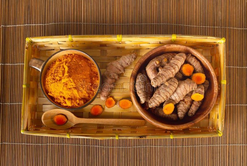Kurkumawortels en poeder in de hoogste mening van de bamboeplaat royalty-vrije stock afbeelding