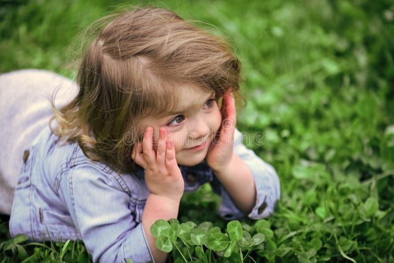 Kurragömma för barnlekar Gulligt barnleende på gräsmatta för grönt gräs royaltyfri fotografi