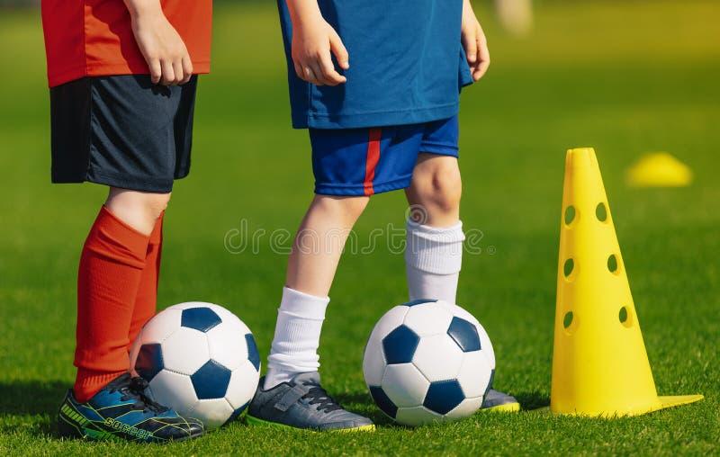 Kurs för fysisk utbildning för fotboll Barn som utbildar fotboll på skolafält arkivbild