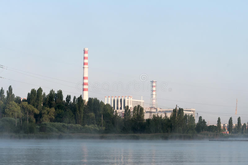 Kursk Nuclear Power Plant reflected in a calm water surface. Mist over the water stock photography