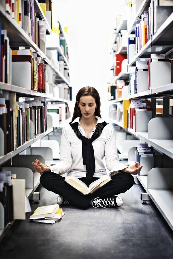 Kursteilnehmer, der über einem Buch in der Bibliothek meditiert. stockfoto