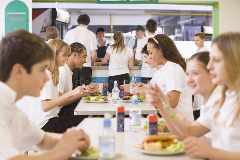 Kursteilnehmer, die in der Schulecafeteria essen stockbild