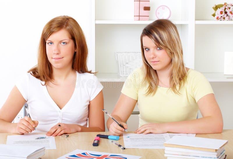 Kursteilnehmer, die am Schreibtisch erlernen lizenzfreie stockbilder