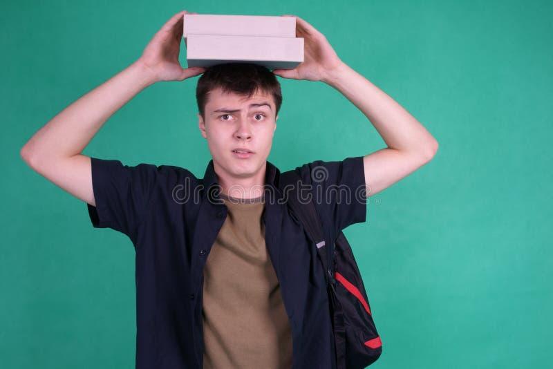 Kursteilnehmer mit schweren Büchern auf seinem Kopf lizenzfreie stockfotos