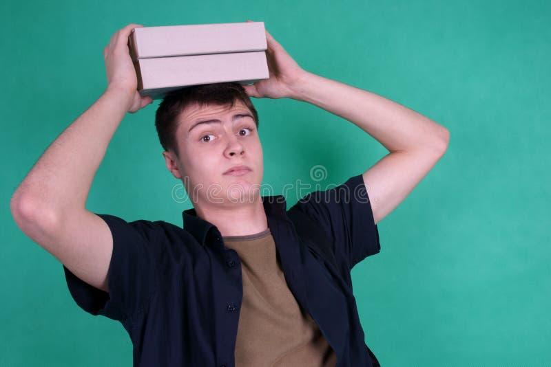 Kursteilnehmer mit schweren Büchern auf seinem Kopf stockfoto