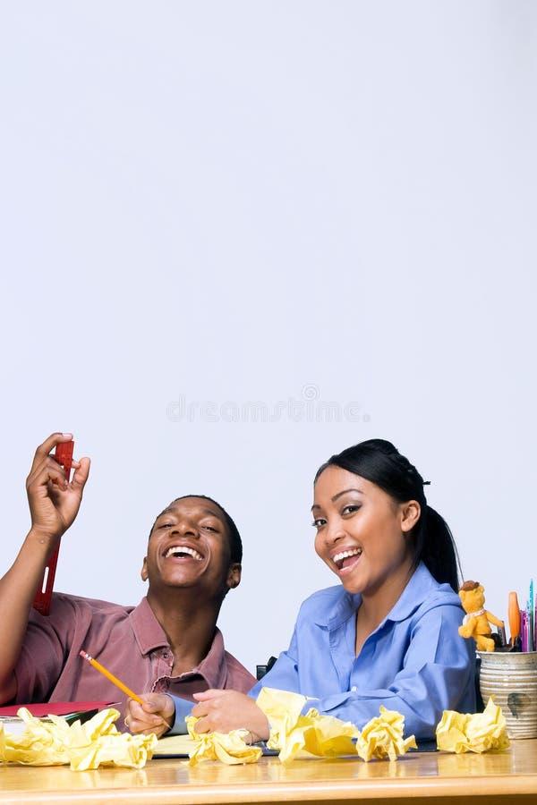 Kursteilnehmer am Schreibtisch mit zerknittertem Papier - Vertikale lizenzfreie stockbilder