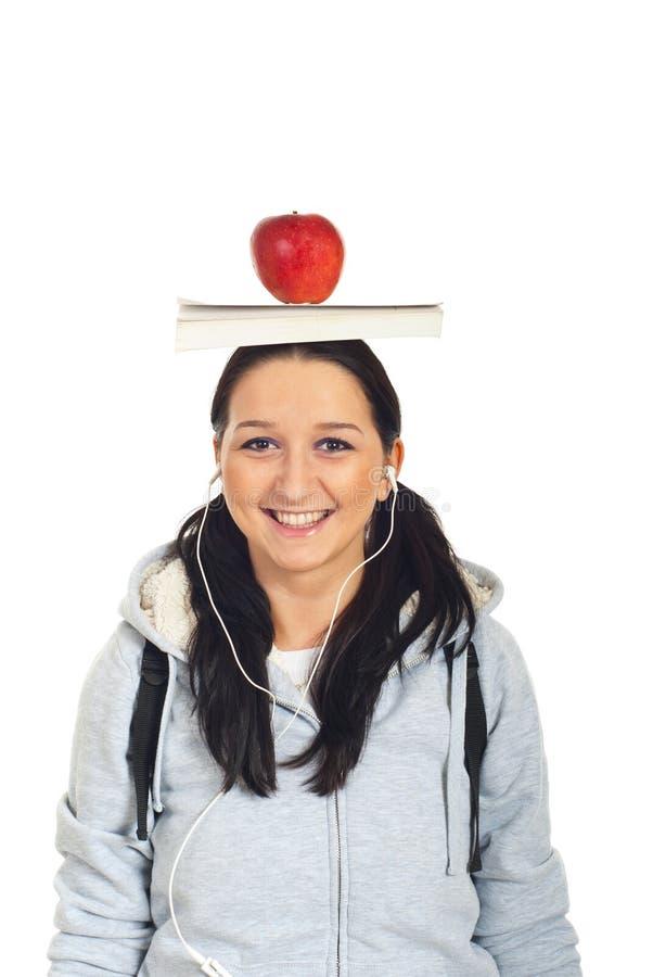 Kursteilnehmermädchen mit Buch und Apfel auf Kopf stockfotos