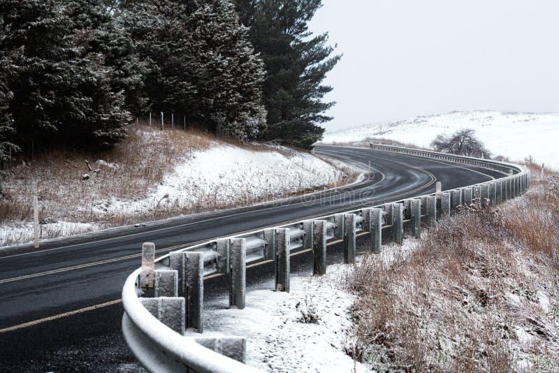 Kurven der Straße durch Schnee bedeckte Hügel stockbild