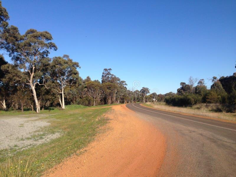 Kurven der Straße mit Bäumen, Sand und blauem Himmel in West-Australien lizenzfreie stockfotografie