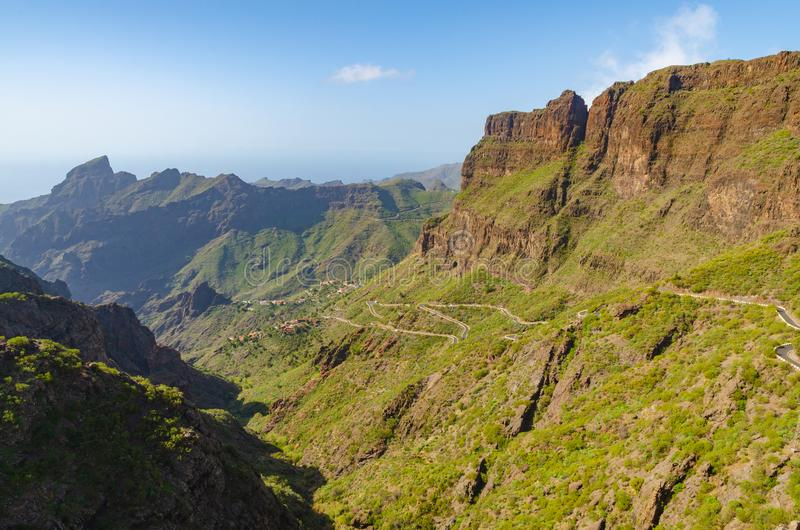 Kurvenreiche Straße, die zu ein kleines Dorf zwischen den Bergen führt stockfotos