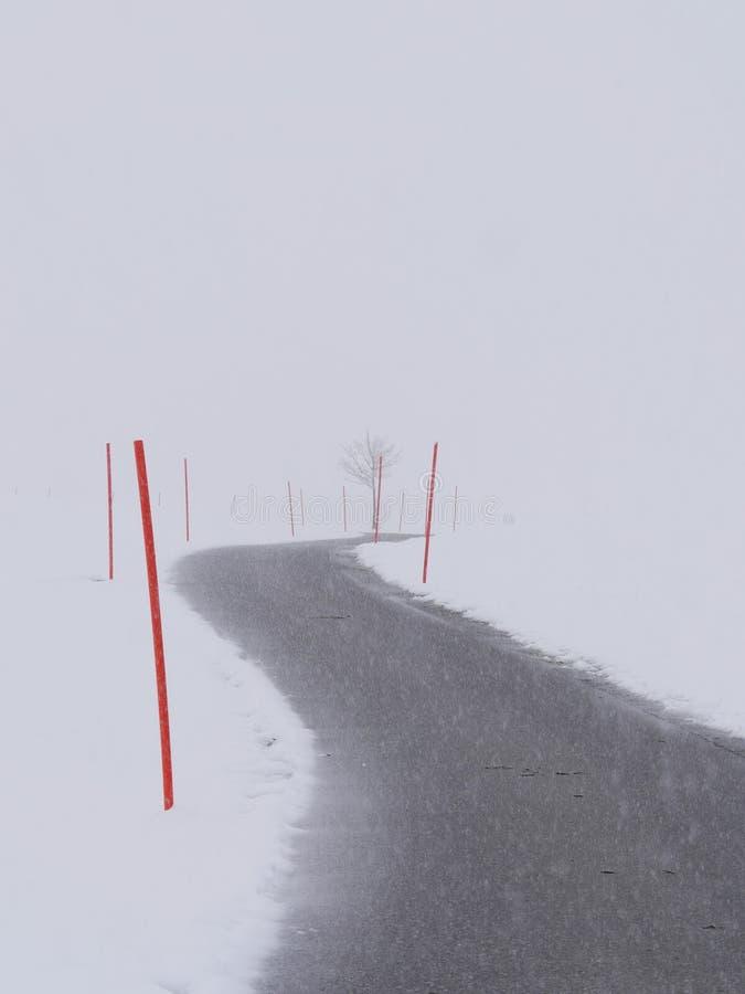 Kurvenreiche Straße durch eine schneebedeckte Landschaft stockfotos