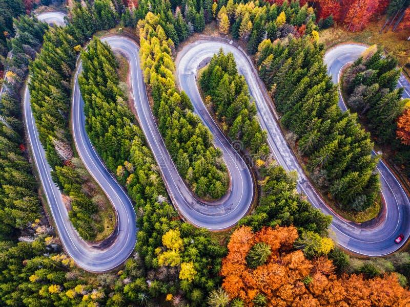 Kurvenreiche Straße vom hohen Gebirgspass, in der Herbstsaison, mit orange Wald lizenzfreie stockbilder