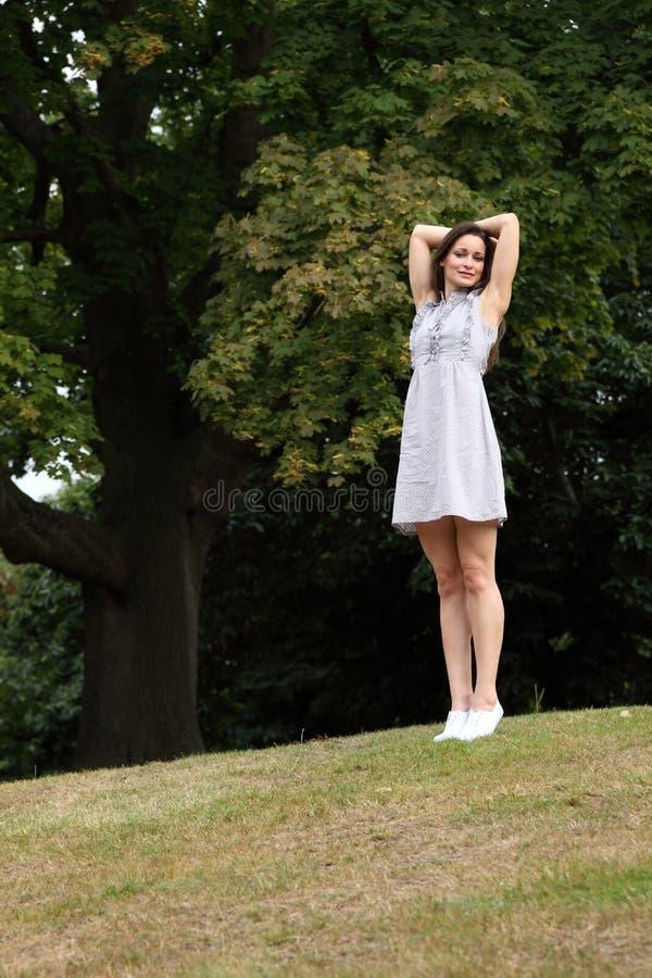 Kurzschlusssommerkleid der jungen Frau, das im Wald steht lizenzfreies stockfoto