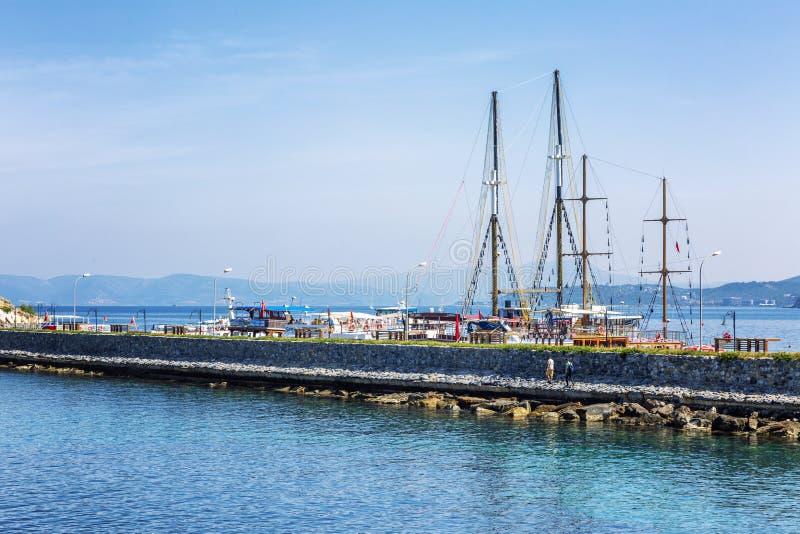 Kusadasi,土耳其,05/19/2019:码头在海用咖啡馆和餐馆 度假者由美好的自然围拢 免版税库存照片