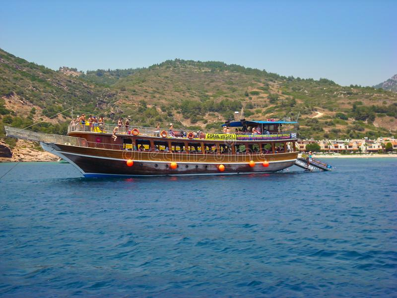 Kusadasi,土耳其- 2012年6月17日:获得的游人在海滩附近停住的一条小巡航小船的乐趣 库存图片
