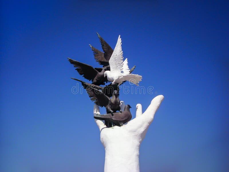 Kusadasi,土耳其- 2012年6月17日:雕塑,手,黑白鸠在Kusadasi,土耳其 和平纪念碑的手 免版税库存图片