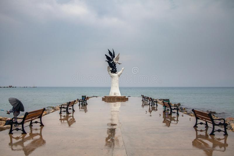 Kusadasi, Turkey - September 17, 2019: The hand of peace sculpture with doves on the waterfront in Kusadasi, Turkey stock image