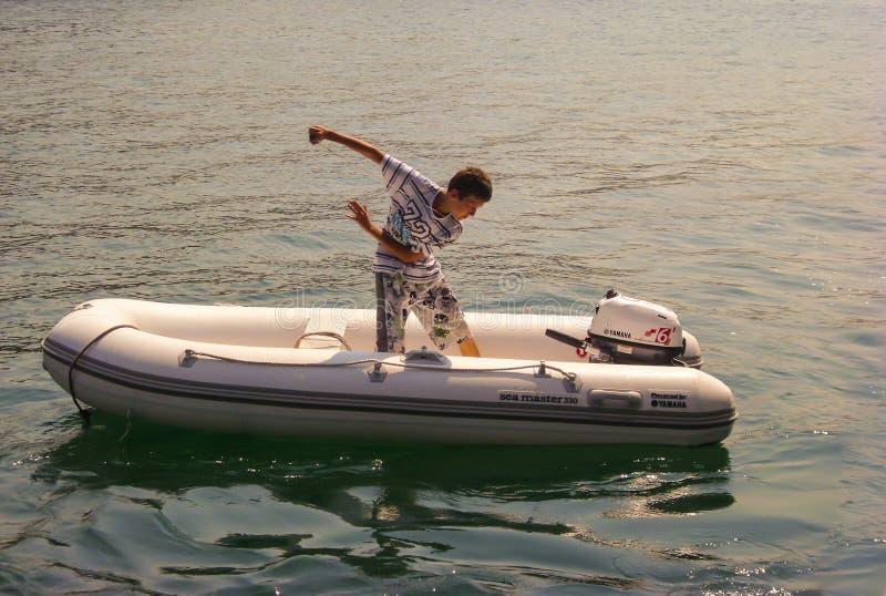 Kusadasi, Turquie - 17 juin 2012 : un garçon met en marche le moteur extérieur du bateau gonflable image libre de droits
