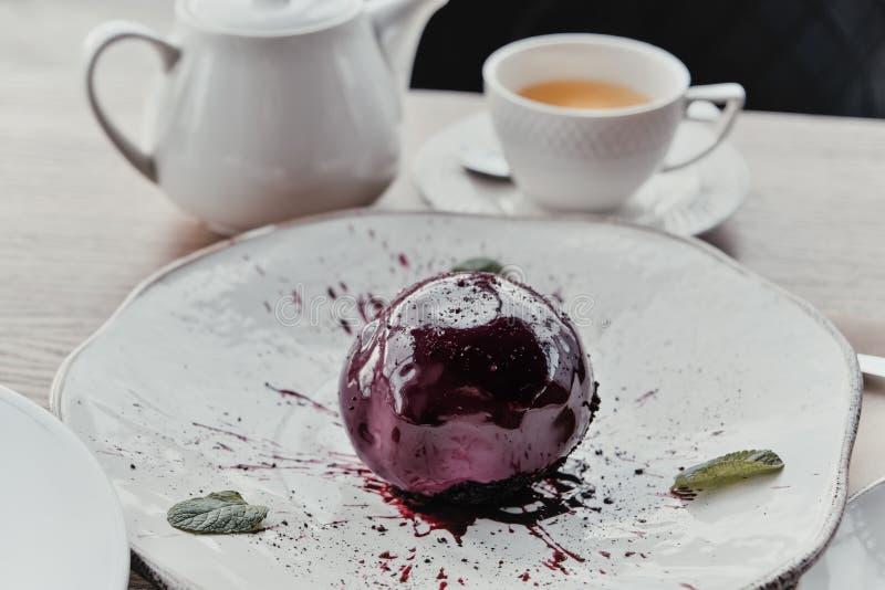 Kuschelförmige Mousse glasierte Dessert, Käsekuchen mit Schokolade und Minze auf der weißen Platte Köstliches Dessert für den Url lizenzfreies stockbild