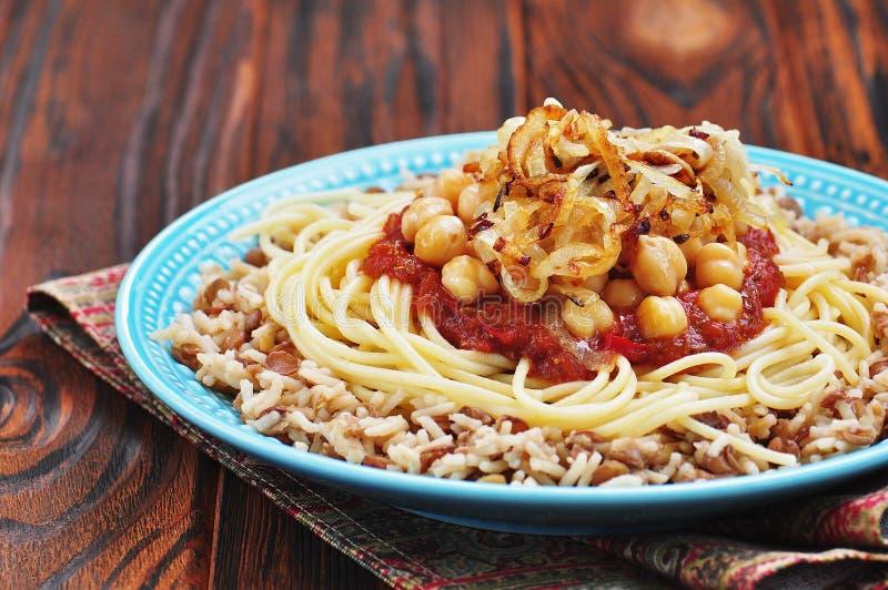 Kushari - plat égyptien des lentilles, du riz, des pâtes, des pois chiches avec la sauce tomate et des oignons croustillants photo libre de droits