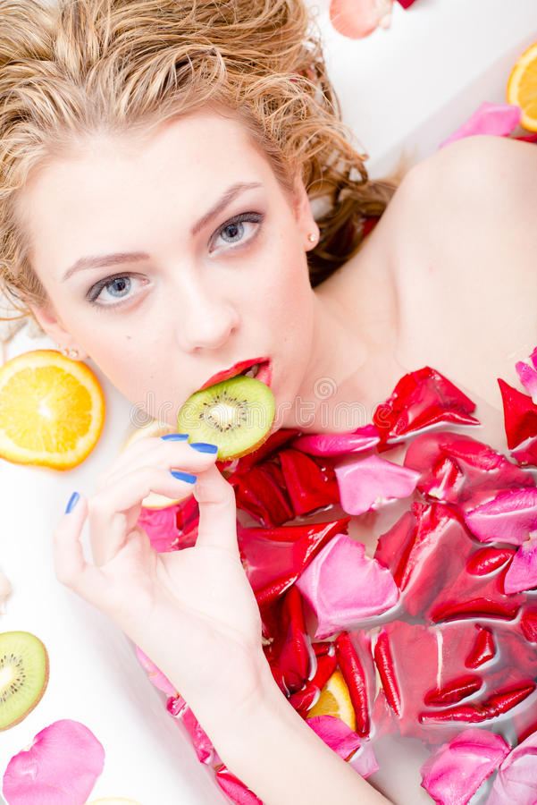 Kusicielska piękna młoda blond seksowna kobieta gryźć kawałek kiwi zbliżenia portret w skąpaniu z kwiatów płatkami obraz royalty free