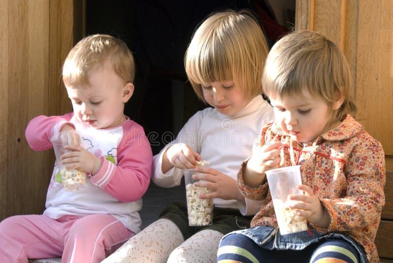 kusiner som äter popcorn arkivfoto