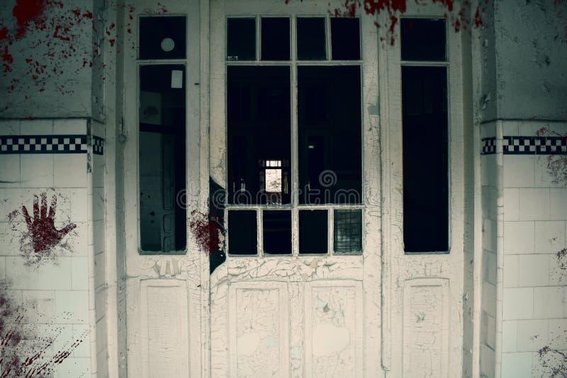 Kuslig blodig dörr av den spökade asylen Övergiven och murken byggnad av det psykiatriska sjukhuset royaltyfri bild