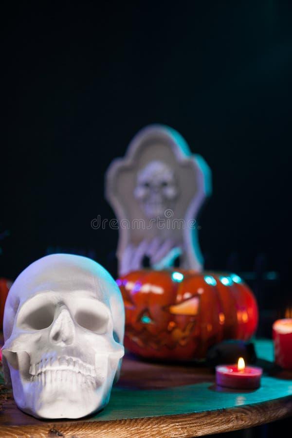 Kuslig mänsklig skalle med andra halloween garneringar på en trätabell royaltyfri foto