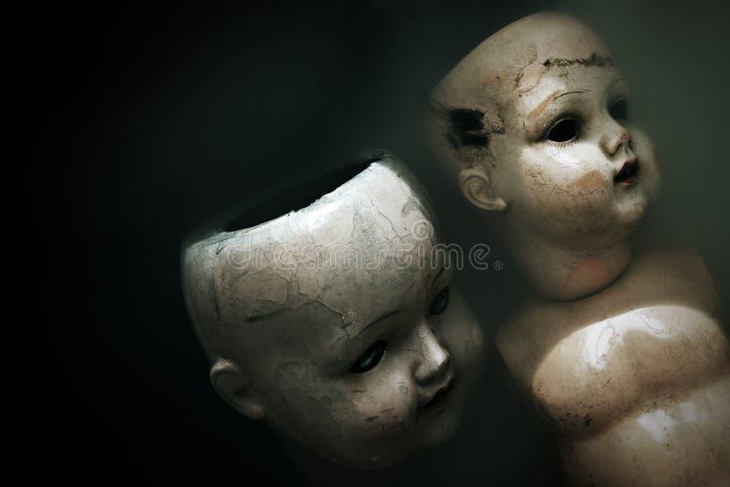 Kusliga dockor i mörker smutsar ner vatten arkivfoton